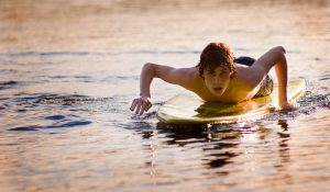 teen boy on a surf board at sunset
