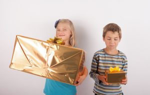 Siblings comparing their presents. The girl is happy with a big gift box while her bother having a small one is very upset.